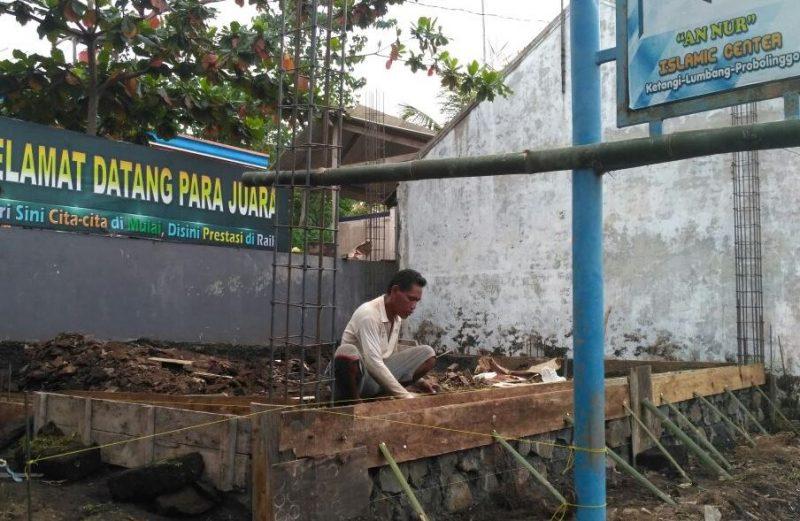 Seorang pekerja sibuk membangun Menara Katangi PCM Lumbang, Kabupaten Probolinggo
