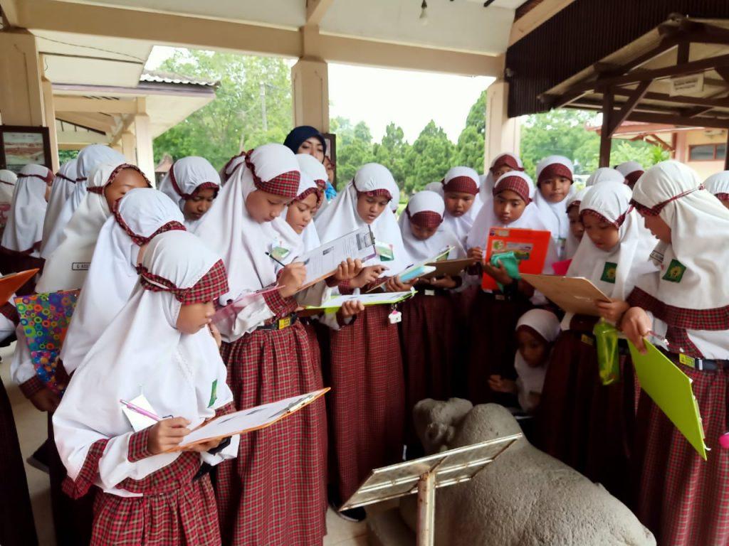 Siswa Berlian School memperhatikan benda peninggalan sejarah di Museum Trowulan Mojokerto. (Rif'atut Tamamiyah/PWMU.CO)