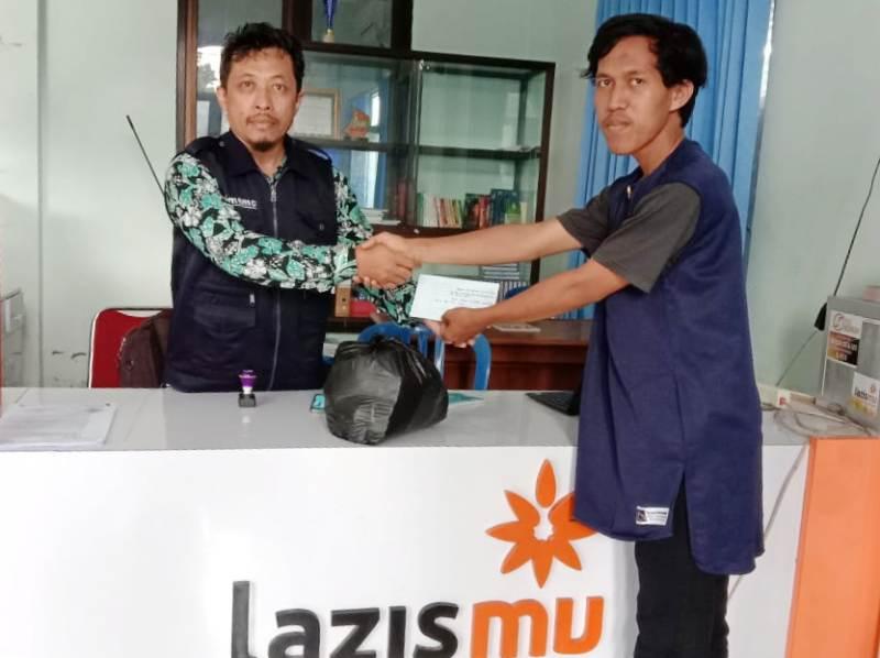 Ketua PC IMM Pacitan Gita Reformasi, kanan, menyerahkan donasi Jabodetabek ke Lazismu. (Isa/PWMU.CO)