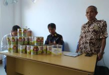 Ketua Lazismu Lumajang Drs Muari bersama para amil melabeli kaleng 3S di kantor. (Said Romdhon/PWMU.CO)