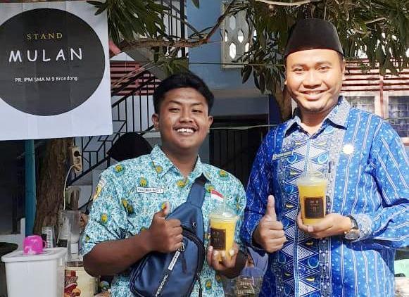 Kepala SMAM 9 Brondong Fazlur Rohman, kanan, bersama siswa membeli Mulan Drink. (Dennis Nugroho/pwmu.co)