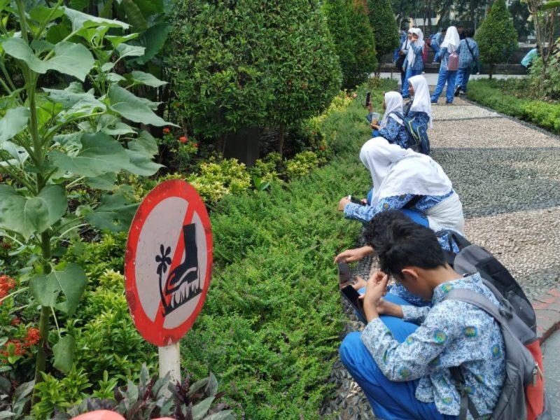 Siswa SMP Muda Surabaya praktik memotret objek lewat HP di taman kota.