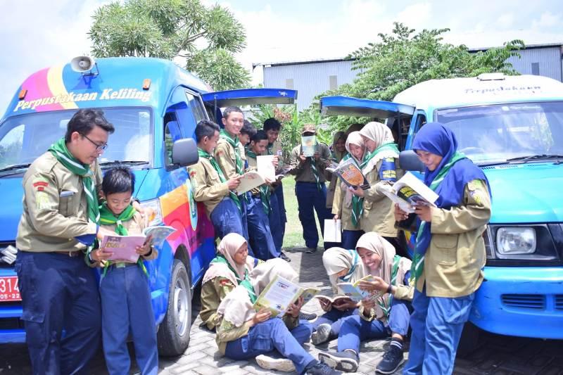 Budaya literasi pandu Hizbul Wathan Lamongan di Musyda dengan membaca buku di Perpustakaan Keliling. (Fathan Faris Saputro/ pwmu.co)