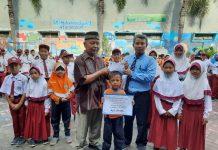 Kholiq Idris, kanan, menyerahkan hasil gerakan infak kepada Kasdi disaksikan siswa SD Muwri. (Mufidatul Latifah/PWMU.CO)