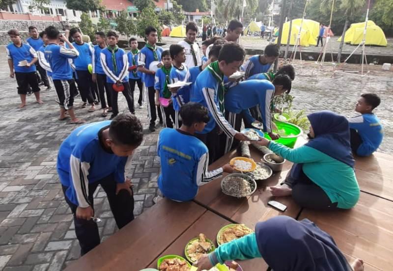 Simulasi pembagian makanan di pengungsian dalam Perkemahan HW SMP Muhammadiyah 4 Giri. (Dimas Hasbi/PWMU.CO)