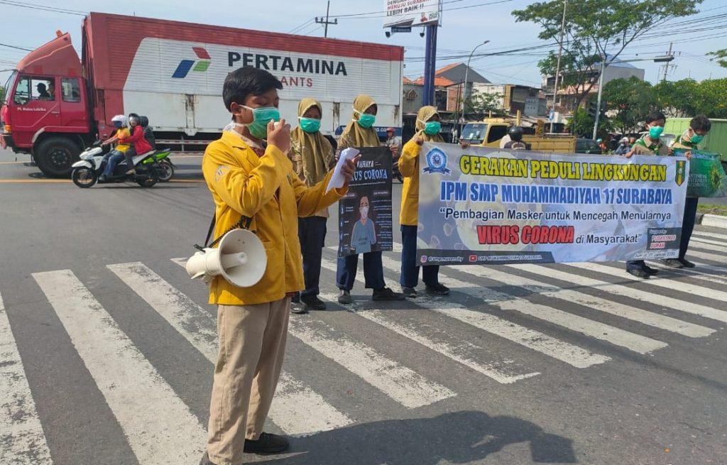Cegah corona yang mematikan siswa SMPM 11 Surabaya membagikan masket pada pengendara sepeda motor di sekitar Jalan Demak Surabaya.