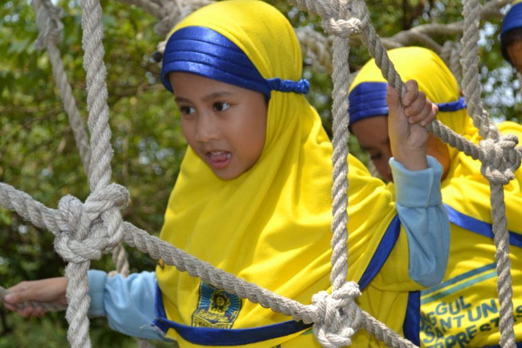 Salah satu siswi kelas I SDM 18 Mulyorejo Surabaya meniti jembatan brima sebagai salah satu wahana permainan di Alas Prambon, Sidoarjo (Mitha Rizky Rachmawati/PWMU.CO)