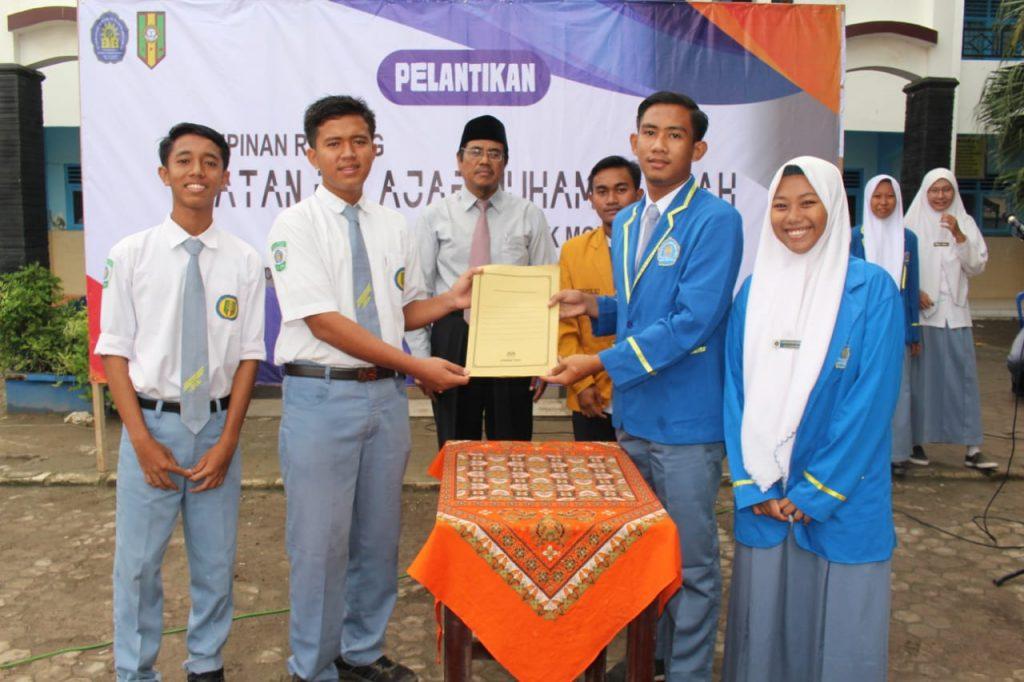 Kepala MAMDA Paciran Moh Hasan Rasidi (tiga dari kiri) menyaksikan serah terima jabatan antara ketua IPM lama (kanan) kepada ketua IPM baru (kiri (Maftuhah/PWMU.CO)