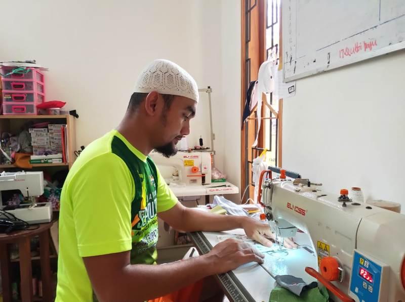Pengusaha konveksi Dony Andri  Setiawan menjahit masker untuk wabah Corona. (Uzlifah/PWMU.CO)