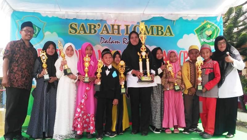 Ketua Aisyiyah Babat Utara Siti Naimul Faizah,paling kanan, bersama Kepala SDN Banaran, tengah, dan murid-muridnya. (Hilman/PWMU.CO)