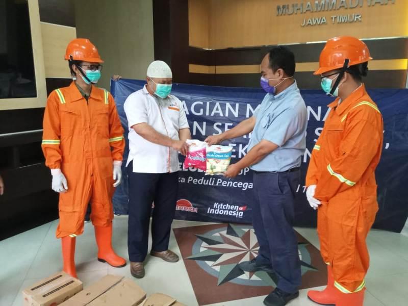 Ketua Lazismu Jatim Zainul Muslimin, kiri, menerima produk olahan laut dari manajer Logistik PT KML M. Faris. (Sugeng/PWMU.CO)