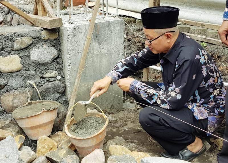 MIM 1 Kota Probolinggo membangun gedung baru ditandai pemasangan batu fondasi oleh Ketua PDM Masfu'. (Hanafi/PWMU.CO)