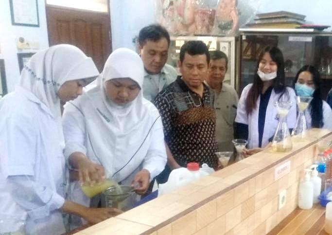 Siswa Smamita membuat hand sanitizer dari aloe vera disaksikan Ketua PDM Mashud, tengah. (Emil/PWMU.CO)