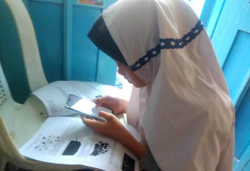 Bilqis Salsabila, siswa SMPM 13 mengerjakan ujian sekolah online di rumahnya. (Nurkhan/PWMU.CO)