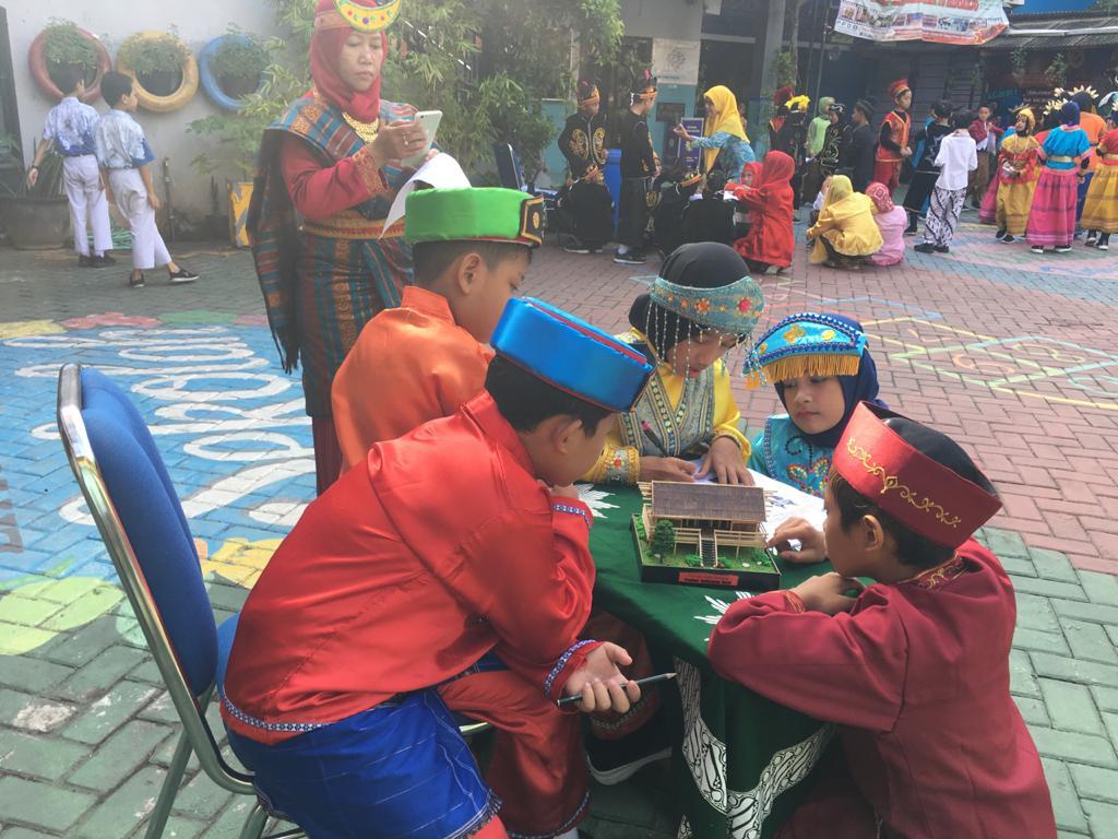 SD Muhida belajar keragaman Indonesia. Seperti yang dilakukan para siswa saat mengamati miniatur rumah adat di halaman sekolah, Rabu (4/3/20).