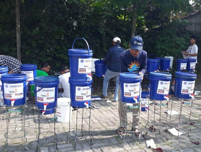 Tim menyiapkan bak air untuk Gerakan Cuci Tangan Lazismu-MDMC Bojonegoro. (M. Shofi/PWMU.CO)