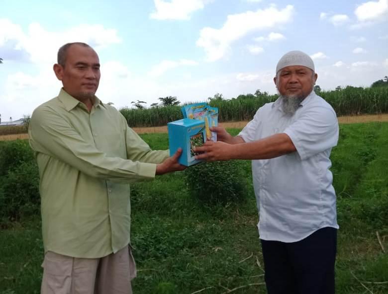 Sudarsono, kiri, menyerahkan benih sayuran kepada Zainul Muslimin untuk program ketahanan pangan. (Aditio/PWMU.CO)