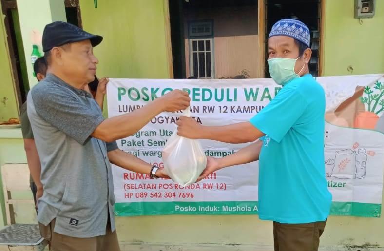 Ketua RW 12 Nitikan Shidiq Anshori, kiri, membagikan paket sembako ke warga. Lumbung pangan ini kerja sama dengan PRM Nitikan. (Affan/PWMU.CO)