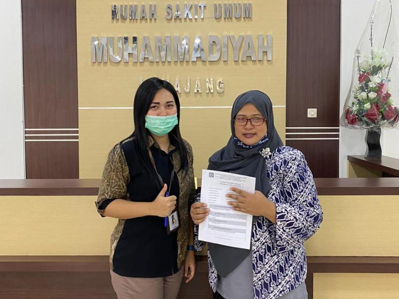 Staf BRI Nofrina Putri, kiri, menyerahkan bantuan diterima Wakil Direktur RS Muhammadiyah Lumajang Enny Kurniawati. (Kuswantoro/PWMU.CO)