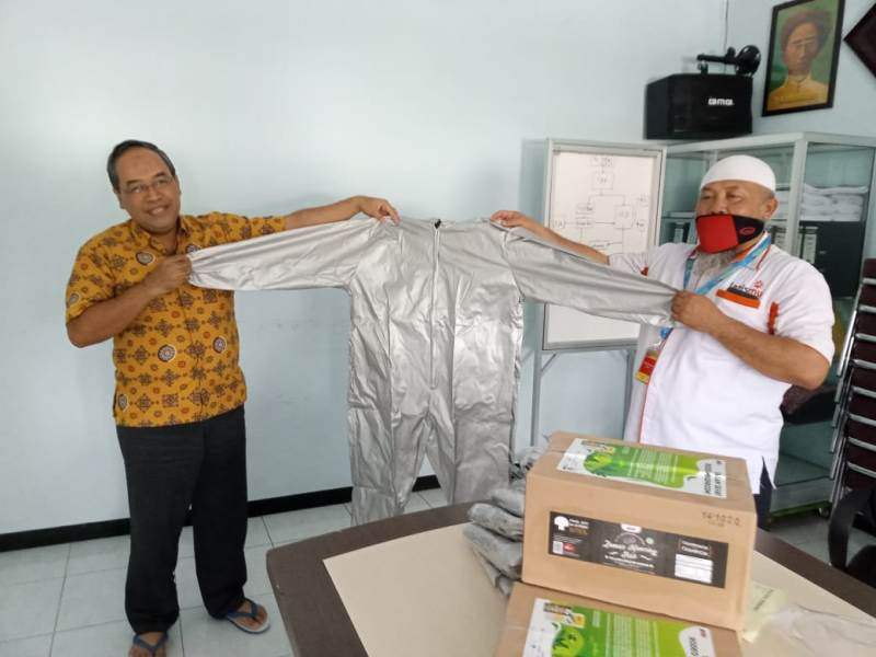Direktur RSIAM Kota Probolinggo dr Fuadi Siham, kiri, menerima pakaian hazmat dari Zainul Muslimin. (Ridho/PWMU.CO)