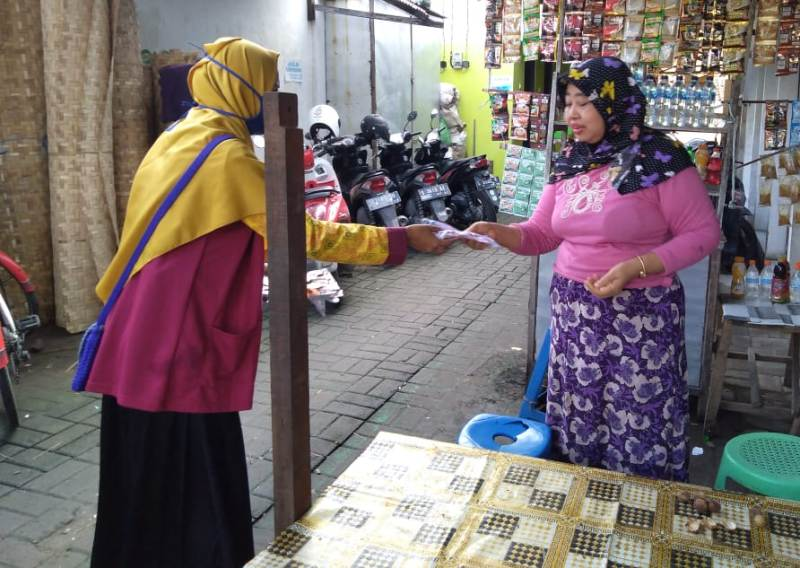 Aktivis IPM Kedungadem membagikan masker ke pedagang pasar. (Ferry/PWMU.CO)