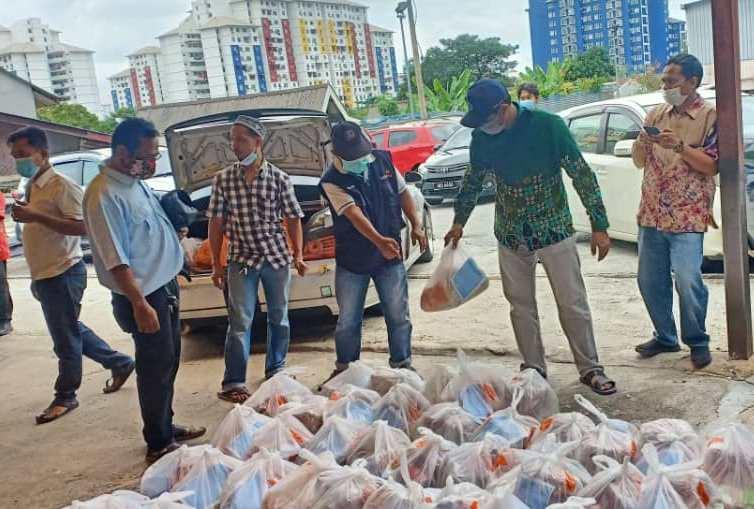 Aliansi Organisasi Masyarakat Indonesia di Malaysia (AOMI) membagikan sembako ke Pekerja Migran. (Sonny Zulhuda/PWMU.CO)