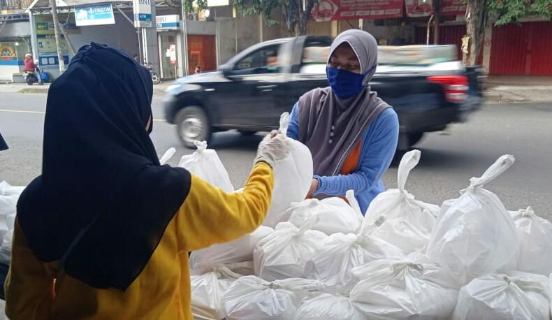 Takjil on the road dilaksanakan SMAM 8 Gresik dan IPM dengan membagikan makanan dan minuman secara gratis pada warga yang melintas di pertigaan Jalan Morowudi Cerme Gresik, Selasa (19/05/20 ).