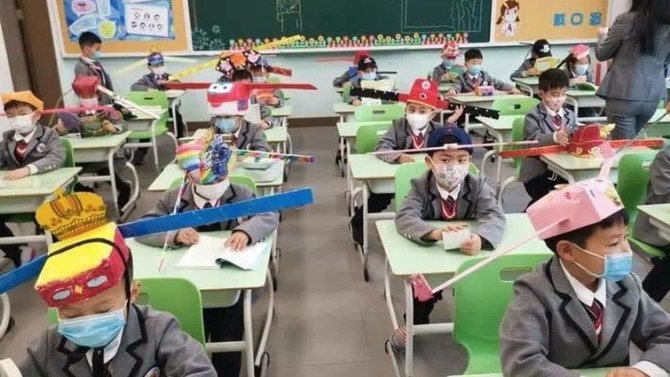New normal di SD Wuhan memakai topi bertanduk untuk jaga jarak.