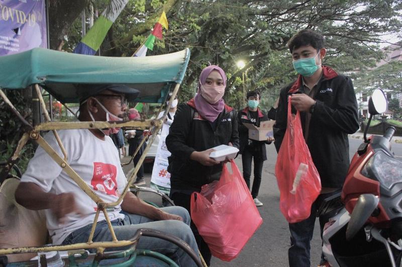 Mahasiswa KKN UMM membagi makanan ke warga dhuafa.