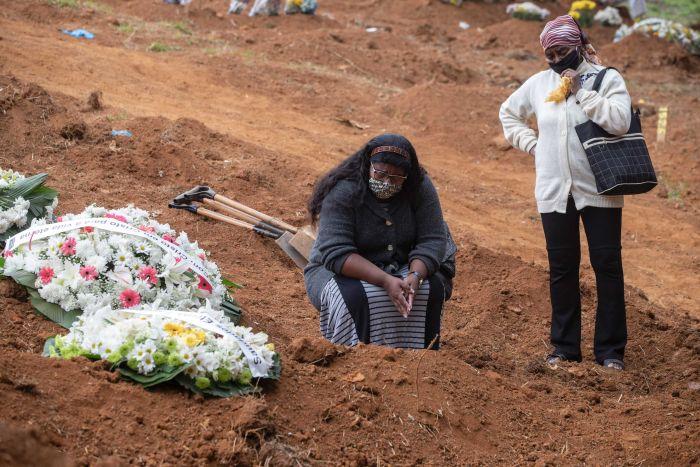 Warga Brasil berdoa di makam kerabatnya yang meninggal akibat covid-19. (foto ap)