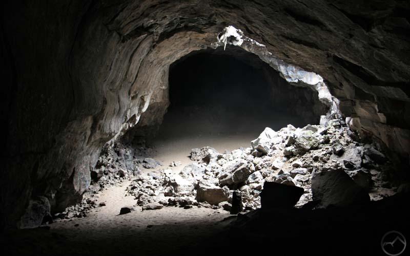 Ilustrasi tiga orang terjebak di gua berdoa tawasul dengan amal saleh.