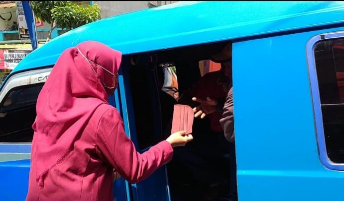 Peringati Kemerdekaan, mahasiswa UMM bagi masker. Dua Mahasiswa Universitas Muhammadiyah Malang (UMM) bergerak ke Terminal Landungsari Kota Malang, Senin (17/8/2020).