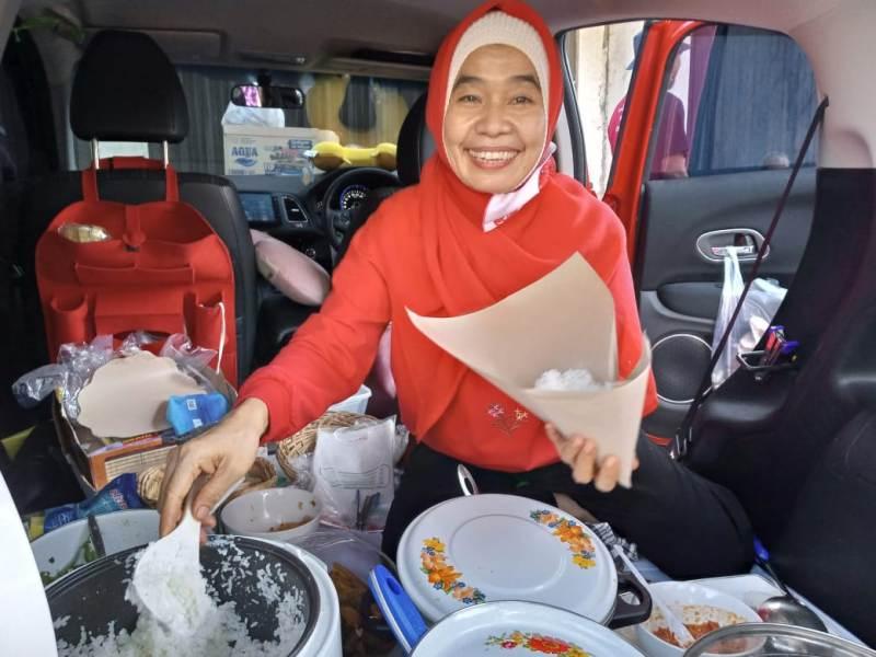 Tan Mei Hwa melayani pelanggan rica-rica menthok pedas di warmobnya. (Sugeng/PWMU.CO)