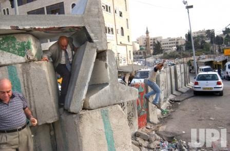 Warga Palestina menerobos celah Tembok Israel. (upi)