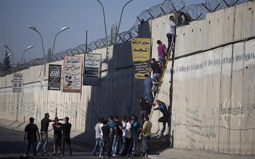 Warga Palestina naiki Tembok Israel untuk mencari kerja.