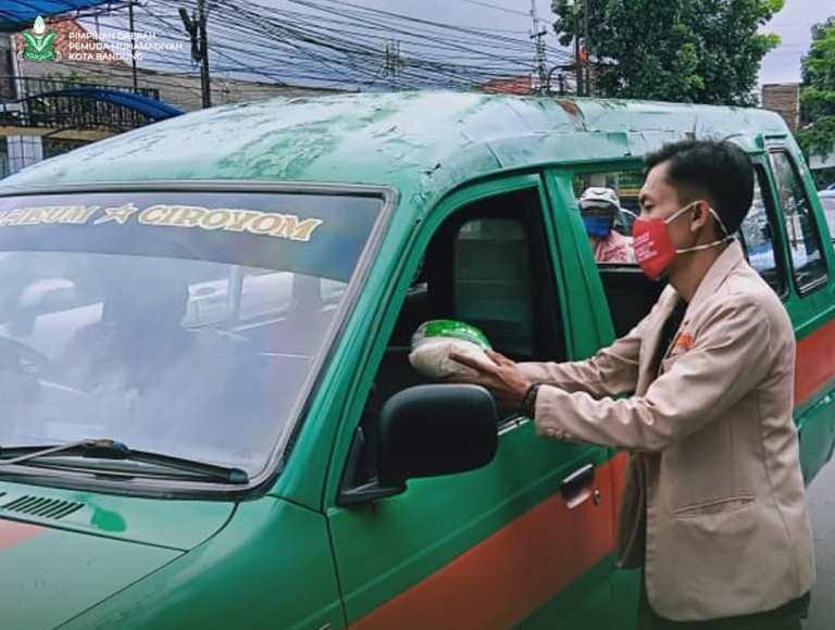 Pemuda Muhammadiyah Kota Bandung bagi-bagi beras pada sopir angkot. Aksi sosial itu menjadi salah satu upaya meredam dampak pandemi Covid-19.