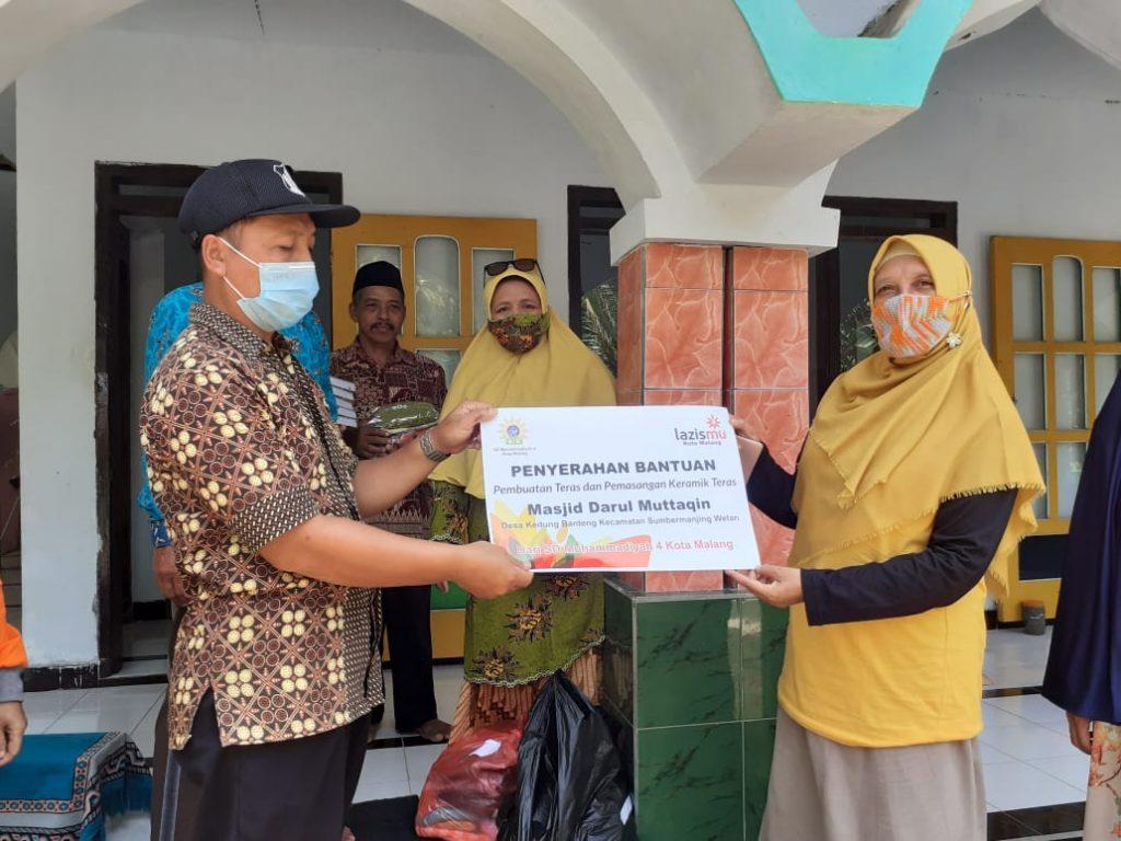 Kepala SD Mupat Malang Hana Ayudah MPd menyerahkan bantuan kepada pengurus Masjid Daarul Muttaqin (Herty/PWMU.CO)